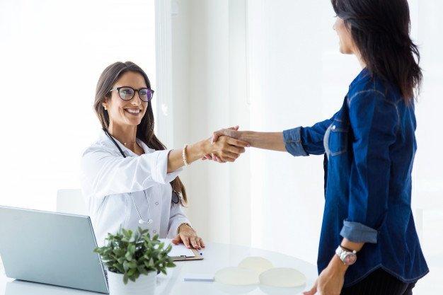 Médica do sexo feminino e seu paciente apertando as mãos na consulta. Foto gratuita